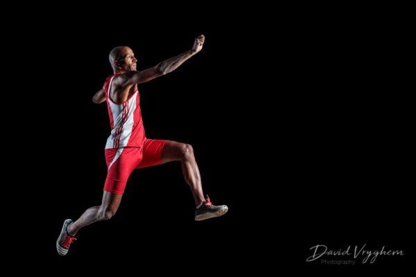 Envol de Josué M'Bon lors d'un saut en longueur, capturé par le photographe sportif à Lausanne et Genève David Vryghem